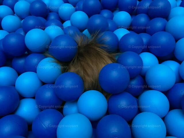 Kind versinkt im Bällebad | Elektrisierte Haare von einem Kind im blauen Bällebad