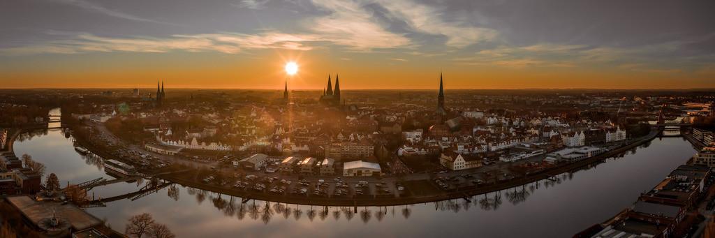 Golden Sunset - Hansestadt Lübeck im Sonnenuntergang  3:1 Panorama | Je nach Tageszeit und Wetterlage entstehen verschiedene Lichtstimmungen. Dieses Mal tauchte die Sonne kurz vor ihrem Untergang die Lübecker Altstadtinsel in ein herrliches, warmes Licht.  Die Bäume entlang des Kanals spiegeln sich im ruhigen Wasser. Eine besondere wohlige Stimmung breitet sich aus.  Dieses Bild kann mit seinen warmen Farbtönen das besondere Highlight an der Wand sein und wir so manchen Betrachter in seinen Bann ziehen.