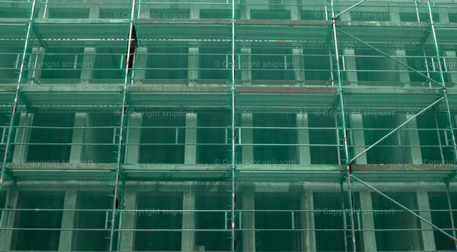 Baustellengerüst   Ein mit grünem Netz abgesichertes Baustellengerüst