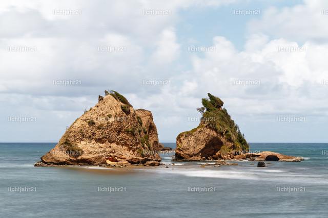 Felsen an der Küste von Dominica | Ausblick zu zwei schroffen Felseninseln in ruhigen Küstengewässern vor bewölktem Himmel mit Wolkenlücke, Wasserbewegung in Langzeitbelichtung  - Location: Karibik, Insel Dominica