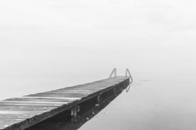 Bootssteg im Nebel | Minimalistisches schwarz-weiß Bild eines Bootsteges am Pelhamer See in Bad Endorf