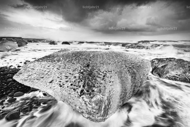 Großer Eisblock in der Brandung | Schwarzweißaufnahme mit großem Eisblock an einem Strand mit starker Brandung, die Wasserbewegung ist zu sehen (Langzeitbelichtung, Bewegungsspuren), weitere Eisblöcke im Hintergrund, darüber ein kontrastreicher bewölkter Himmel - Location: Island, Jökulsarlon (Jökulsárlón)