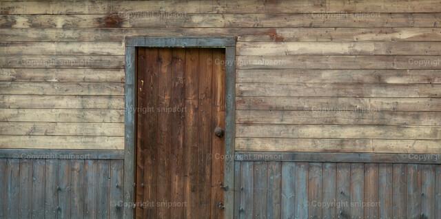 Holzhaus (Detail) | Detail von einer rustikalen Holzhausfassede mit einer Eigangstür.