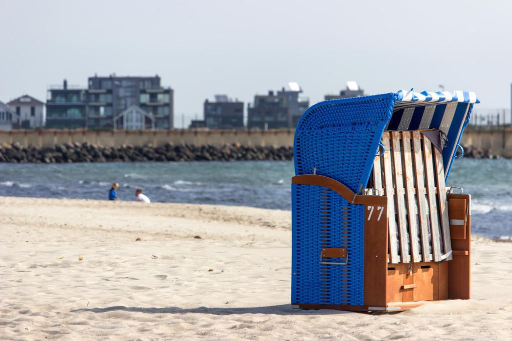 Olpenitz an der Schlei | Strandkorb am Weidefelder Strand im Vordergrund – im Hintergrund kann man die Ferienwohnungen in Olpenitz sehen