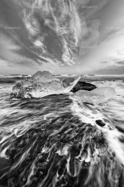 Eisblöcke und Wellen | Schwarzweißbild von Eisblöcken an einem Strand mit starker Brandung, die Dynamik einer Welle ist zu sehen (Langzeitbelichtung, Bewegungsspuren), darüber eine markante dramatisch wirkende Wolkenformation - Location: Island, Jökulsarlon (Jökulsárlón)