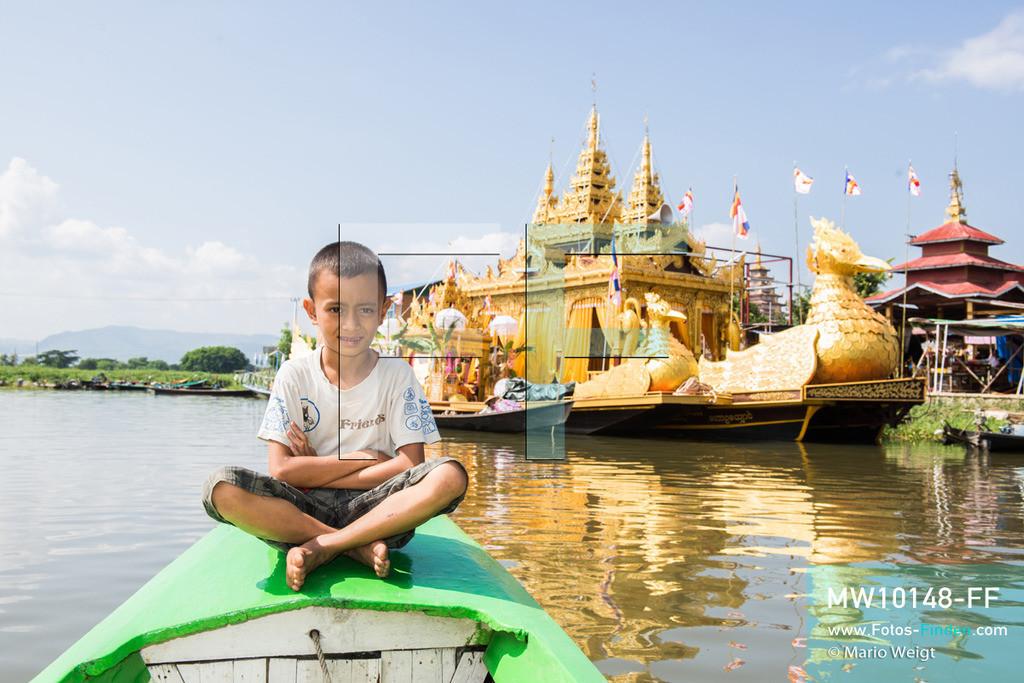 MW10148-FF   Myanmar   Inle-See   Nyaungshwe   Reportage: Ye Lin lebt auf dem Inle-See   Ye Lin auf dem Boot während des Phaung Daw U Festivals. Im Hintergrund ankert die goldene Barke Shwe Hintha an einem buddhistischen Kloster. Der 8-jährige Ye Lin Yar Zar lebt mit seinen Eltern in einem Pfahlhaus auf dem Inle-See. Er gehört zur ethnischen Gruppe der Intha und beherrscht die einzigartige Einbeinrudertechnik, um zur Schule zukommen.  ** Feindaten bitte anfragen bei Mario Weigt Photography, info@asia-stories.com **