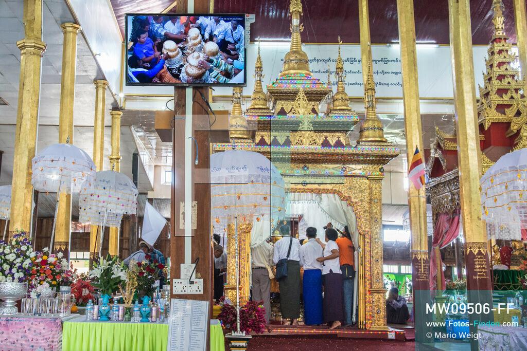 MW09506-FF | Myanmar | Nyaung Shwe | Reportage: Phaung Daw U Fest | Ein Dorfkloster während des Festivals auf dem Inle-See. Nur die Männer dürfen Goldplättchen den vier Buddha-Statuen spenden. Um den Altar häufen sich die Spendengaben.   ** Feindaten bitte anfragen bei Mario Weigt Photography, info@asia-stories.com **