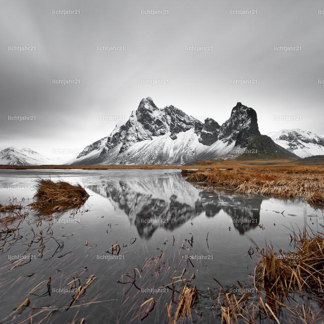 Bergkette mit Spiegelung | Schneebedeckte Bergformation spiegelt sich in einem Teich, Grasbüschel im und neben dem Teich, Grashalme werden teilweise vom Wind bewegt, Wolkenbewegung wird durch Langzeitbelichtung sichtbar, große Tiefenwirkung - Location: Island, Südküste