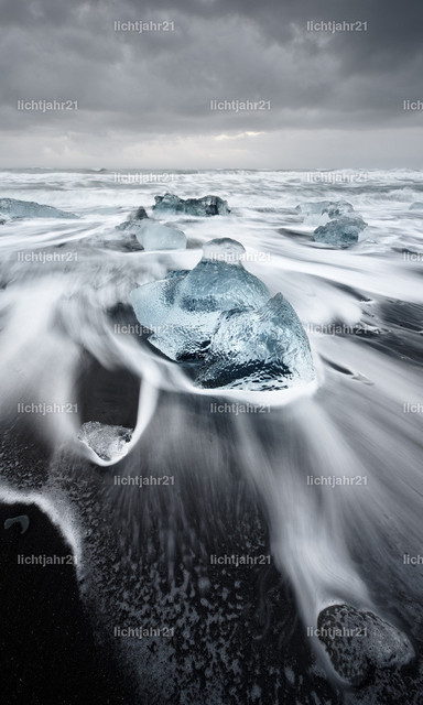 Eisblöcke in der Brandung | Eisblöcke in blauen Farbtönen an einem schwarzen Strand mit starker Brandung, die Wasserbewegung ist zu sehen (Langzeitbelichtung, deutliche Bewegungsspuren), darüber ein kontrastreicher grau bewölkter Himmel, Tiefenwirkung durch Perspektive - Location: Island, Jökulsarlon (Jökulsárlón)