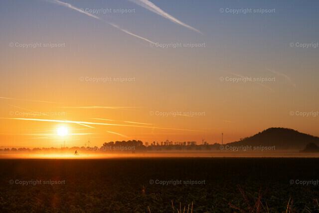 Ein durch den Nabel fahrender Radfahrer | Vom Sonnenaufgang golden schimmernder Nebel, durch den ein Radfahrer fährt