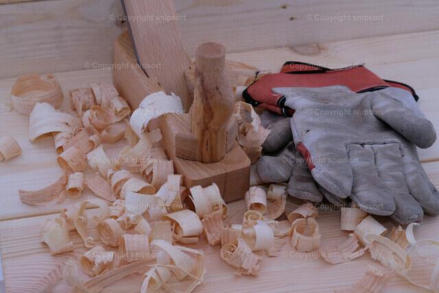 Feierabend in der Tischlerei | Hobel mit Holzspänen und Arbeitshandschuhen als Konzept einer Holzwerkstatt