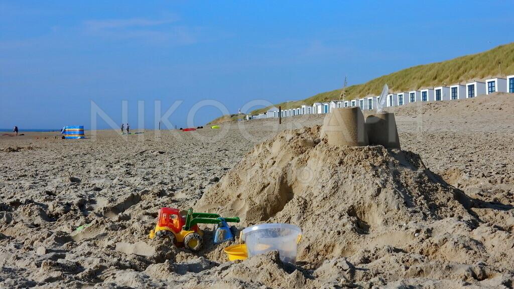Sandburg am Strand | Eine Sandburg am Strand von De Koog auf der Nordseeinsel Texel. Im Hintergrund sind die Strandhütten vor dem Dünengras zu sehen.