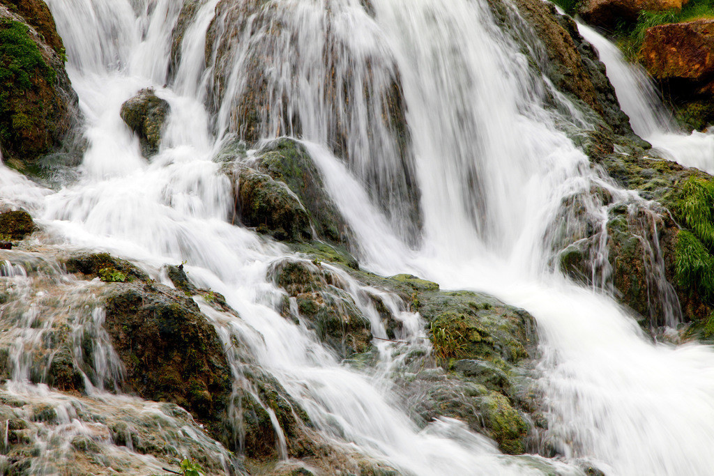 JT-120423-236 | Wasserfall, Wasser eines Baches stroemt bergab, ueber bemooste Steine und Felsen.