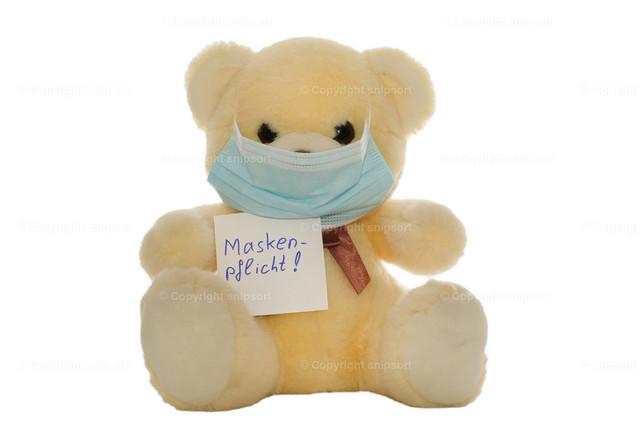 Plüschbär mit Mundschutzmaske und mit einem Zettel
