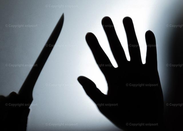 Silhouette eines Einbrechers | Silhouette von einem Messer in der Hand im Gegenflucht als Konzept eines Einbrechers.