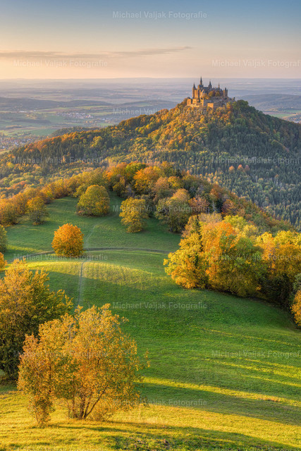 Burg Hohenzollern im Herbst   Die Sonnenstrahlen des späten Nachmittags tauchen die Landschaft und die buntgefärbten Blätter der Laubbäume in ein schönes warmes Licht.