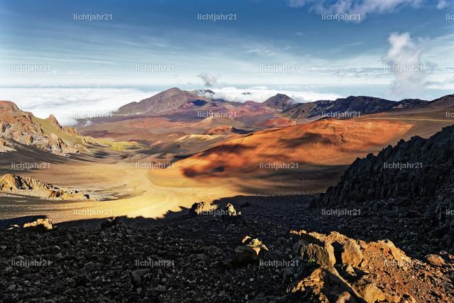 Kraterlandschaft mit markanten Schatten | Kraterlandschaft in ca. 3.000 Metern Höhe mit markanten Schatten und Wolken, vielfältige Farbtöne, im Vordergrund ein großes Geröllfeld - Location: Hawaii, Insel Maui, Vulkan