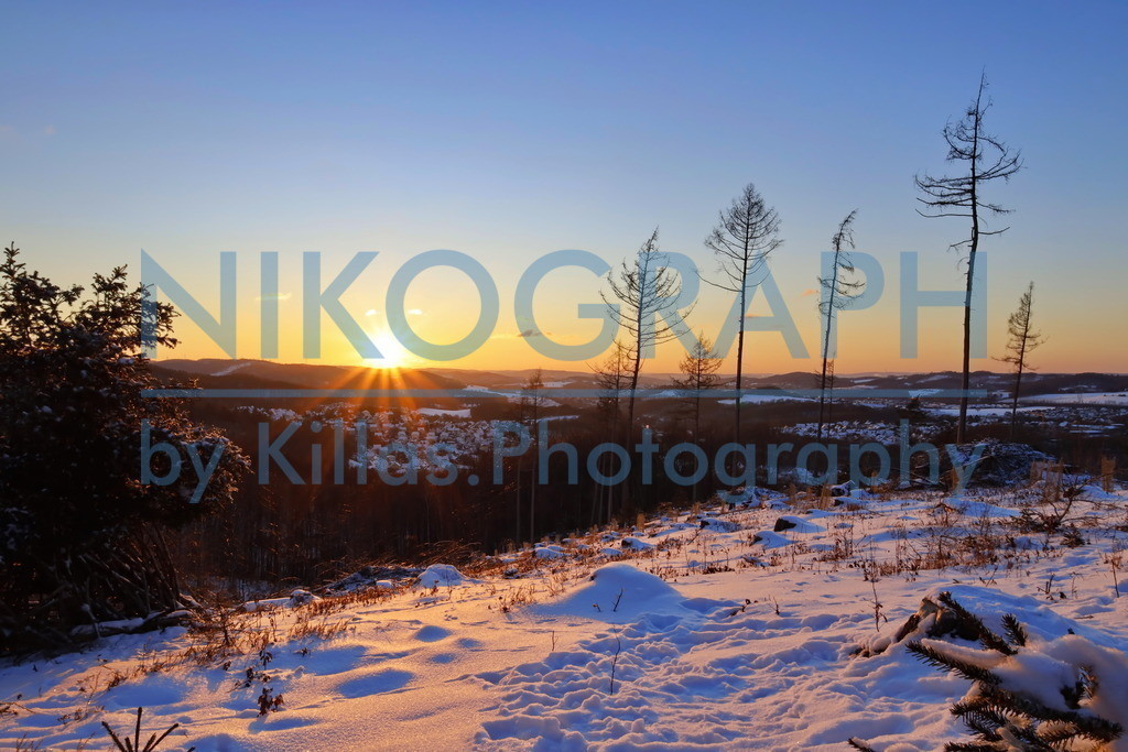 Iserlohner Winterlandschaft | Die Sonne geht hinter dem Iserlohner Stadtteil Roden unter. Die winterliche Szenerie ist im Licht der Abendsonne eingetaucht, die Sonnenstrahlen tauchen den Schnee in ein warmes Licht.