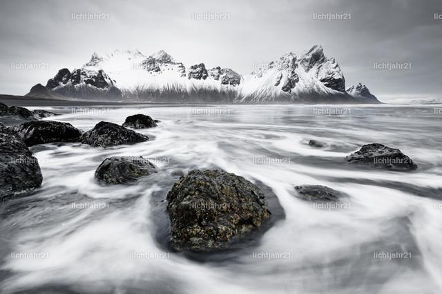 Bergkette vor wilder Brandung | Schneebedeckte Bergformation, die sich im Wasser eines schwarzen Lavasandstrandes spiegelt, im Vordergrund von Wellen umspülte Steine, große Tiefenwirkung - Location: Island, Südküste
