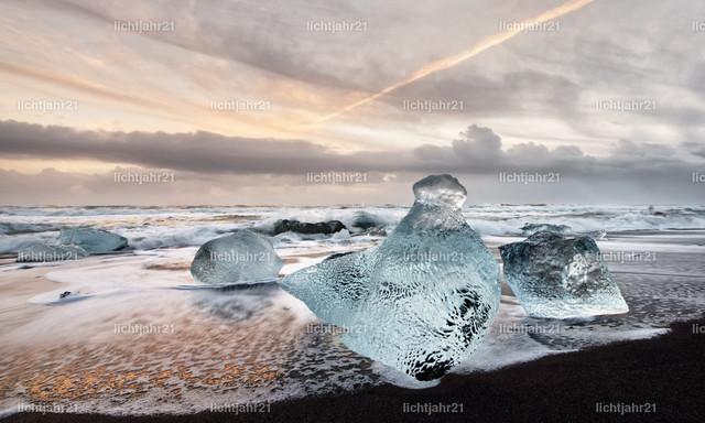 Eisblöcke am schwarzen Strand | Eisblöcke in blauen und dunklen Farbtönen an einem schwarzen Strand mit starker Brandung, das Eis spiegelt sich im nassen Sand, im Hintergrund rollen Wellen heran, Himmel mit farbigem Abendlicht - Location: Island, Jökulsarlon (Jökulsárlón)