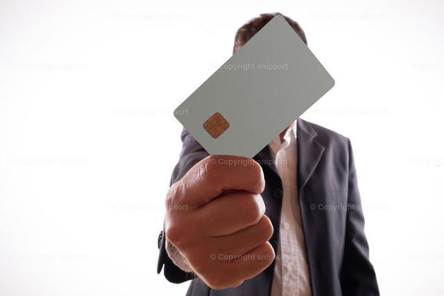 Bankangestellter mit einer Geldkarte mit Chip. | Mann mit Anzug streckt einem eine Bankkarte entgegen