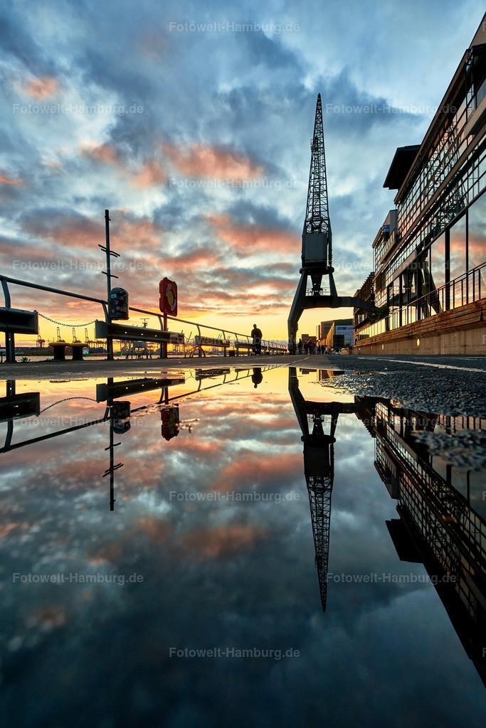 10181001 - Sonnenuntergang gespiegelt | Dramatischer Sonnenuntergang am Hamburger Hafen mit Spiegelung in einer Pfütze