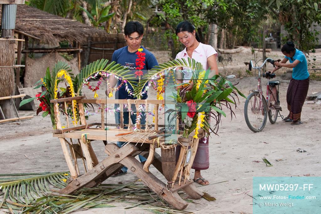 MW05297-FF | Laos | Provinz Sayaboury | Vieng Keo | Reportage: Pey Wan im Elefantendorf | Die ganze Familie hilft beim Dekorieren mit.  Der achtjährige Pey Wan lebt im Elefantendorf Vieng Keo im Nordwesten von Laos. Im Dorf wohnen ca. 500 Leute mit 17 Arbeitselefanten. Sein Vater Hom Peng hat einen 31 Jahre alten Elefantenbullen namens Boun Van, mit dem er im Holzfällercamp im Dschungel arbeitet. Zum Elefantenfest schmückt Pey Wan den Jumbo und darf mit ihm an der Prozession durchs Dorf teilnehmen. Pey Wan möchte, wie sein Vater, später auch Elefantenführer werden.   ** Feindaten bitte anfragen bei Mario Weigt Photography, info@asia-stories.com **
