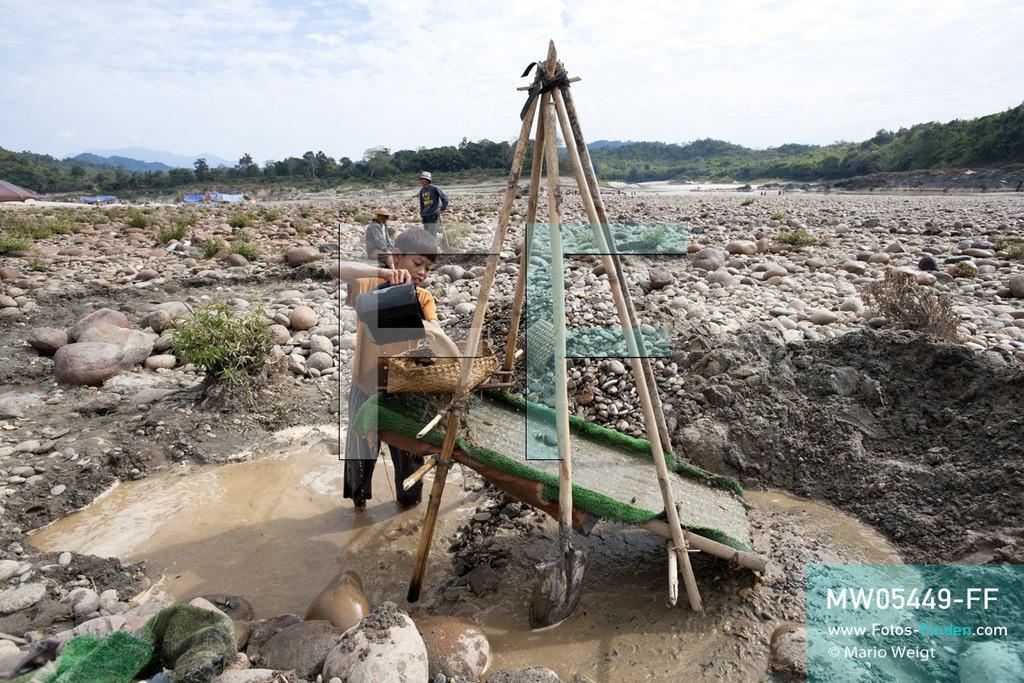 MW05449-FF | Myanmar | Kachin State | Myitson | Adee spült den Flusssand über die Holzrutsche und hofft, dass winzige Goldpartikel in der grünen Matte zurückbleiben. Der 13-jährige Maung Adee lebt mit seiner Tante und seinem Onkel im Dorf Thanphe, drei Kilometer vom Zusammenfluss des Ayeyarwady. Dort schürft Adee mit seiner Familie nach Gold.  ** Feindaten bitte anfragen bei Mario Weigt Photography, info@asia-stories.com **