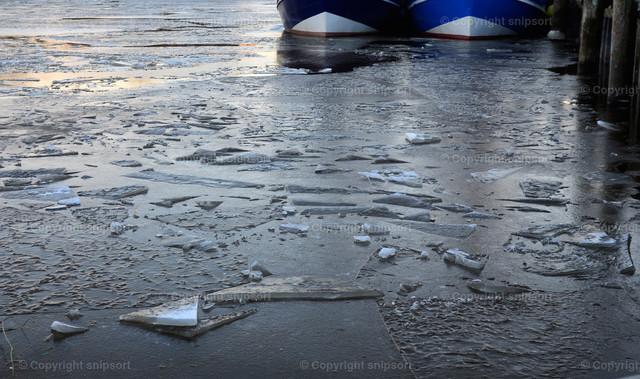 Zugefrorener Hafen | Treibende Eisschollen in einem Hafen.