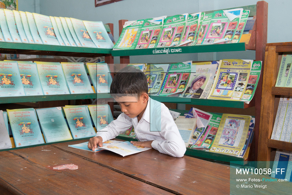 MW10058-FF   Kambodscha   Siem Reap   Reportage: Sombath erkundet Angkor   Sombath liest gern in der Schulbibliothek. Der achtjährige Sombath lebt in Kambodscha im Dorf Anjan, sechs Kilometer westlich von Siem Reap entfernt. In seiner Freizeit nimmt ihn manchmal sein Onkel in die berühmte Tempelanlage von Angkor mit. Besonders mag er die riesigen Wurzeln der Kapokbäume, die auf den uralten Mauern wachsen. Seine Lieblingstempel in Angkor sind Ta Prohm, Banteay Kdei und Preah Khan.  ** Feindaten bitte anfragen bei Mario Weigt Photography, info@asia-stories.com **