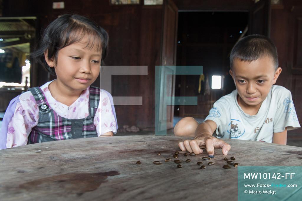 MW10142-FF | Myanmar | Inle-See | Nyaungshwe | Reportage: Ye Lin lebt auf dem Inle-See | Ye Lin spielt mit seiner Schwester Than Dar Aung eine Art Mini-Billard mit Kürbiskernen. Der 8-jährige Ye Lin Yar Zar lebt mit seinen Eltern in einem Pfahlhaus auf dem Inle-See. Er gehört zur ethnischen Gruppe der Intha und beherrscht die einzigartige Einbeinrudertechnik, um zur Schule zukommen.  ** Feindaten bitte anfragen bei Mario Weigt Photography, info@asia-stories.com **