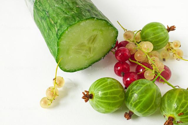 Gesunde vegane Ernährung | Eine aufgeschnittene, frisch gewaschene Gurke mit roten und weißen Johannisbeeren und grünen Stachelbeeren