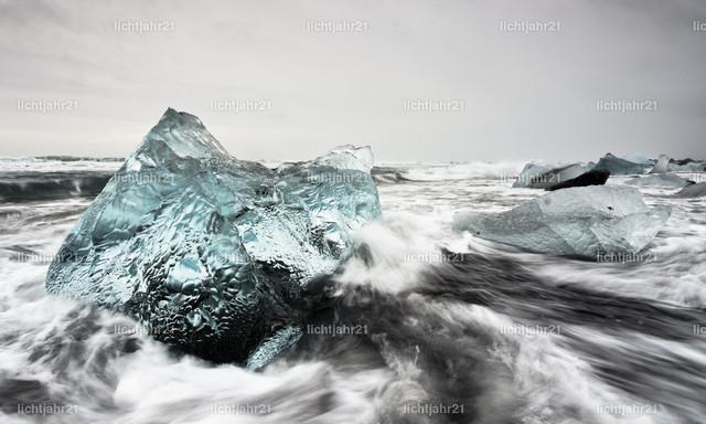 Eisblock in starker Brandung | Markanter Eisblock an einem schwarzen Strand mit starker Brandung, Bewegungsspuren des Wassers auf dem dunklen Sand, im Hintergrund weitere Eisblöcke, Wellen rollen heran, kontrastreicher Himmel mit Wolken und etwas Farbe - Location: Island, Jökulsarlon (Jökulsárlón)