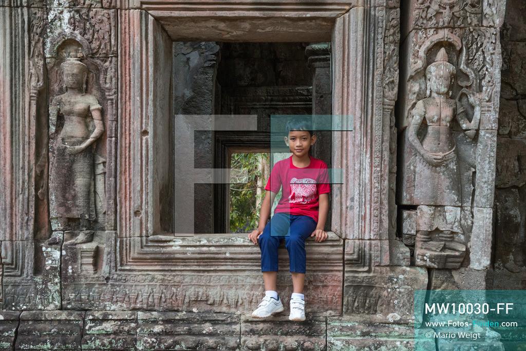 MW10030-FF | Kambodscha | Siem Reap | Reportage: Sombath erkundet Angkor | Sombath im Tempel Banteay Kdei.  Der achtjährige Sombath lebt in Kambodscha im Dorf Anjan, sechs Kilometer westlich von Siem Reap entfernt. In seiner Freizeit nimmt ihn manchmal sein Onkel in die berühmte Tempelanlage von Angkor mit. Besonders mag er die riesigen Wurzeln der Kapokbäume, die auf den alten Mauern wachsen. Seine Lieblingstempel in Angkor sind Ta Prohm, Banteay Kdei und Preah Khan.  ** Feindaten bitte anfragen bei Mario Weigt Photography, info@asia-stories.com **