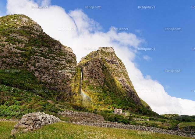 Azoren - Wasserfall auf der Insel Flores  | Großer Wasserfall mit Regenbogen auf der Azoren-Insel Flores, steile imposante Felswand, blauer Himmel mit Wolken, ein Wahrzeichen der Insel - Location: Azores, Flores Island, Faja Grande, Ribeira das Casas