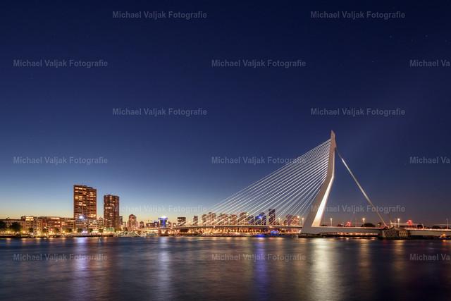 Rotterdam Skyline   Blick über die Nieuwe Maas zu einem der Wahrzeichen von Rotterdam - die Erasmusbrücke. Vor allem nach Sonnenuntergang, kurz bevor es komplett dunkel und der Himmel gerade noch etwas blau ist, wirkt sie am besten, da jedes Stahlseil mit einem eigenen Scheinwerfer angeleuchtet wird und sie sich so optimal vom Hintergrund abhebt. Etwas links davon ist noch das letzte Licht der Dämmerung zu sehen und auch die ersten Sterne erscheinen schon am Firmament.