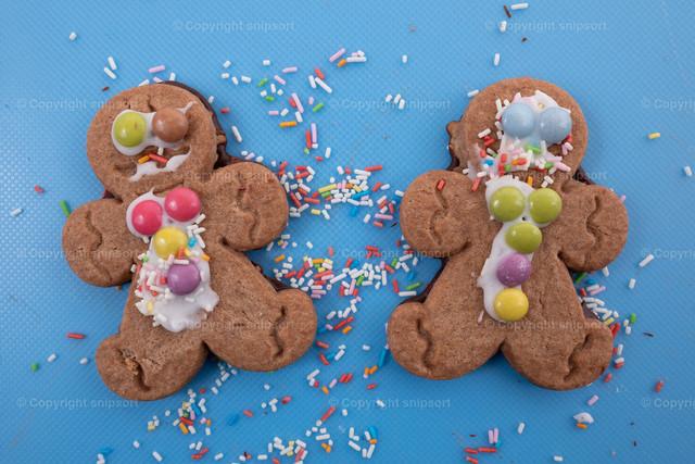 Zwei als Männchen geformte Kekse | Zwei als Kekse geformte Männchen mit Zuckerstreusel über blauem Hintergrund.