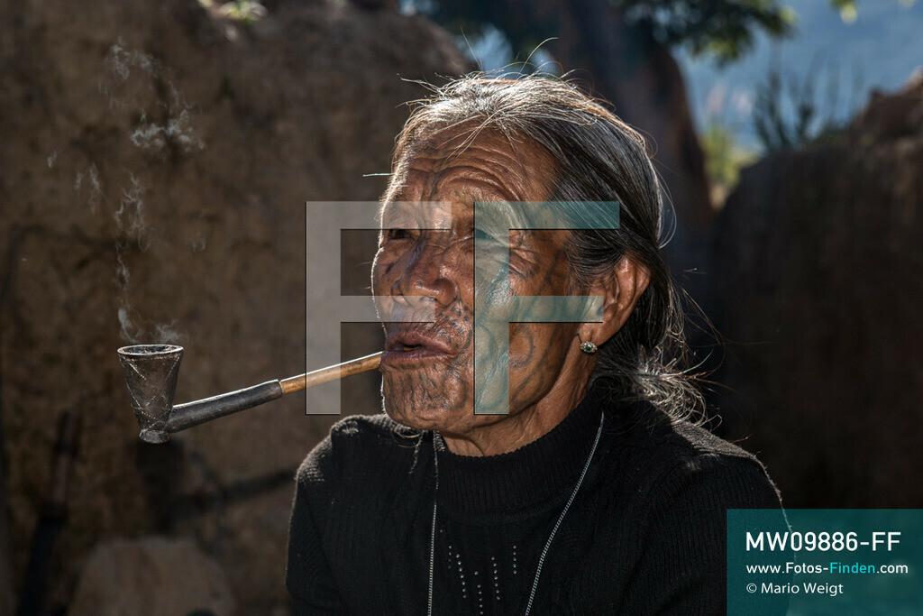 MW09886-FF | Myanmar | Mindat | Reportage: Mindat im Chin State | Pfeife rauchende Frau der Volksgruppe der Muun im Bergdorf An Laung. Die Muun sind eine Untergruppe der Chin. Charakteristisch für die Muun-Frauen ist die Gesichtstätowierung mit zahlreichen Halbkreisen an Wangen, Streifen an Nase und Kinn sowie Punkten.   ** Feindaten bitte anfragen bei Mario Weigt Photography, info@asia-stories.com **