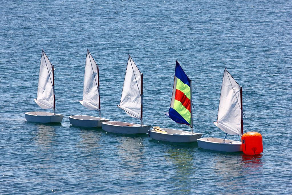 Segelboot   Kleine Segelboote der Optimisten-Klasse, an einer Boje. Gehoeren zu einer Segelschule. Segelunterricht fuer Kinder.