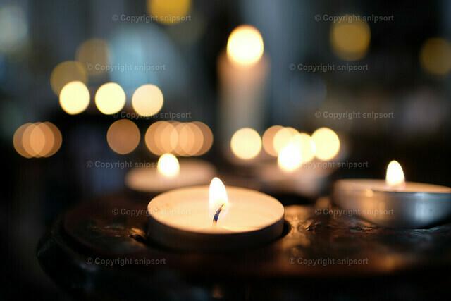 Opferlichter | Detail von brennenden Kerzenlichtern in einer Kirche.