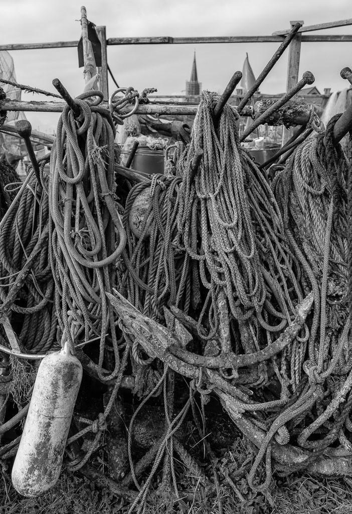 Auf einer Landungsbrücke am Holm in Schleswig © Holger Rüdel | Die Landungsbrücken am Holmer Strand sind grasbewachsene Anleger der Schleswiger Fischer. Hier machen sie seit Jahrhunderten ihre Boote fest und lagern ihr Material wie diese Anker, Taue und Fender.