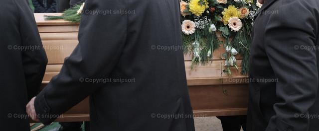 Beerdigung | Sargträger tragen einen mit Blumen geschmückten Sarg zu Grabe