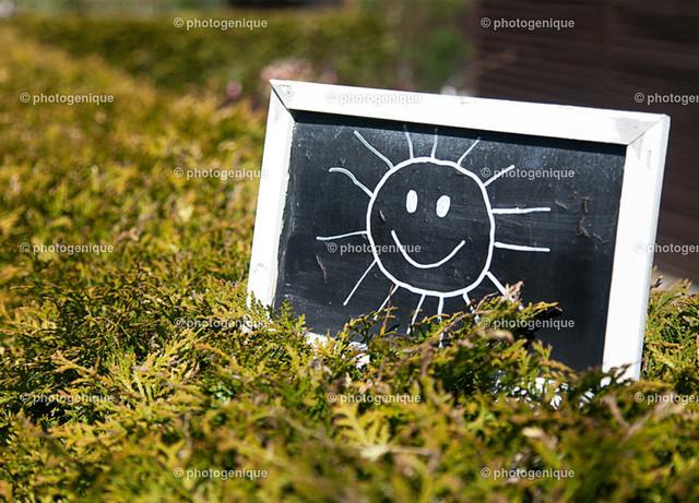 Postkarte Die Sonne lacht | eine lachende Sonne ist mit Kreide auf eine kleine Tafel gemalt, die auf einer grünen Hecke steht