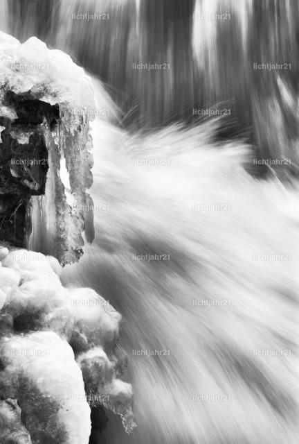 Wasserfall mit Eis in Detailansicht | Detailansicht von fließenden Wasser eines gewaltigen Wasserfalls im Winter, Eiszapfen an den Felsen neben der Kaskade, Langzeitbelichtung, Fließstruktur, Schwarzweißbild - Location: Island, Golden circle, Gullfoss