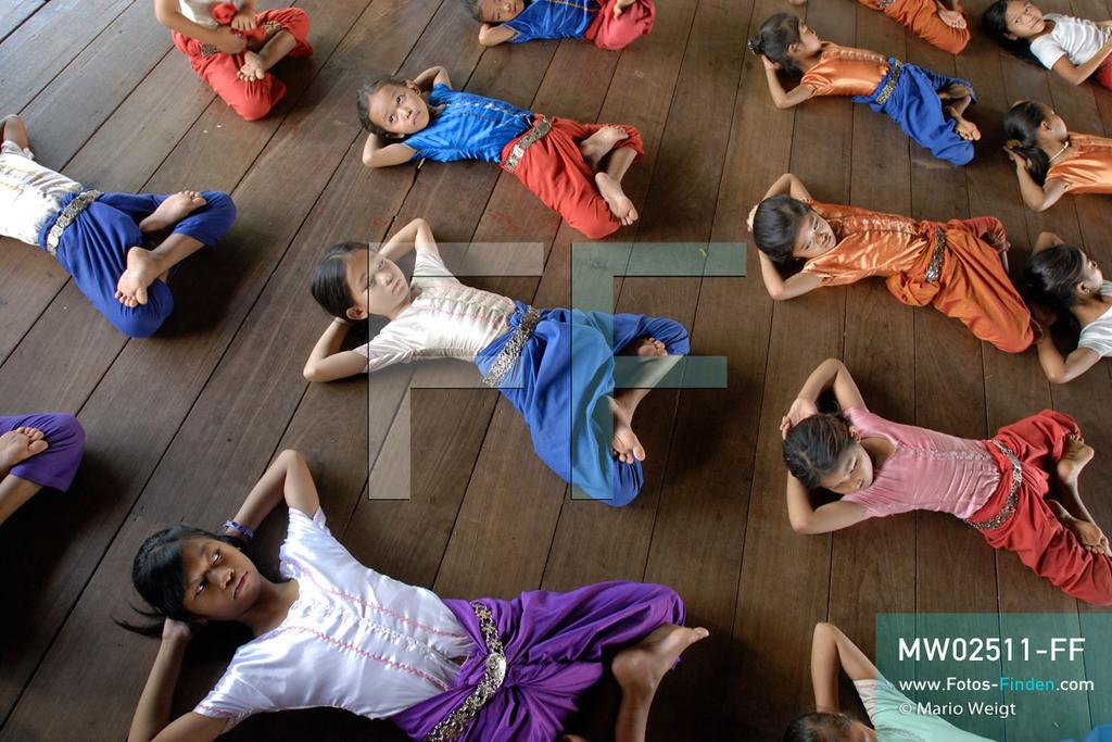 MW02511-FF | Kambodscha | Phnom Penh | Reportage: Apsara-Tanz | Schülerinnen beginnen die Tanzstunde mit Dehnübungen. Sie lernen den Apsara-Tanz in einer Tanzschule. Sechs Jahre dauert es mindestens, bis der klassische Apsara-Tanz perfekt beherrscht wird. Kambodschas wichtigstes Kulturgut ist der Apsara-Tanz. Im 12. Jahrhundert gerieten schon die Gottkönige beim Tanz der Himmelsnymphen ins Schwärmen. In zahlreichen Steinreliefs wurden die Apsara-Tänzerinnen in der Tempelanlage Angkor Wat verewigt.   ** Feindaten bitte anfragen bei Mario Weigt Photography, info@asia-stories.com **