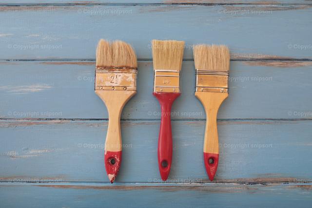 Drei Malerpinsel | Konzept für Malerarbeiten mit Pinseln über blauen Brettern.