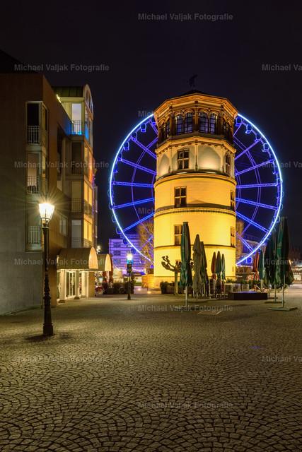 Schlossturm in Düsseldorf und blaues Riesenrad  | Blau beleuchtetes Riesenrad auf dem Burgplatz in der Düsseldorfer Altstadt, mit dem Schlossturm im Vordergrund.