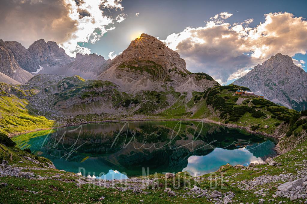 Stark wie ein Drache | Dieses gigantische Bergmassiv verschluckt in diesem Moment die Sonne. Der See spiegelt die Szene ruhig wieder.