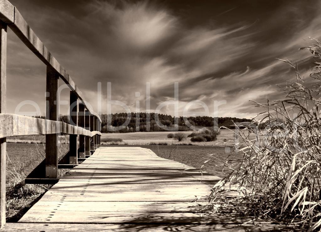 Holzsteg | Landschaft mit Steg und interessantem Wolkenspiel, fotografiert in Ulmen. (Vulkaneifel) Monochrom in warmen Brauntönen. Optional können Sie im Bestellvorgang auch schwarz/weiß auswählen, wie übrigens bei allen Bildern in diesem Shop.