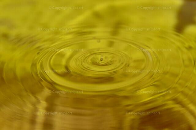 Konzentrische Kreise von einem Tropfen | Ein Tropfen fällt in eine gelbe Flüssigkeit und erzeugt konzentrische Kreise.